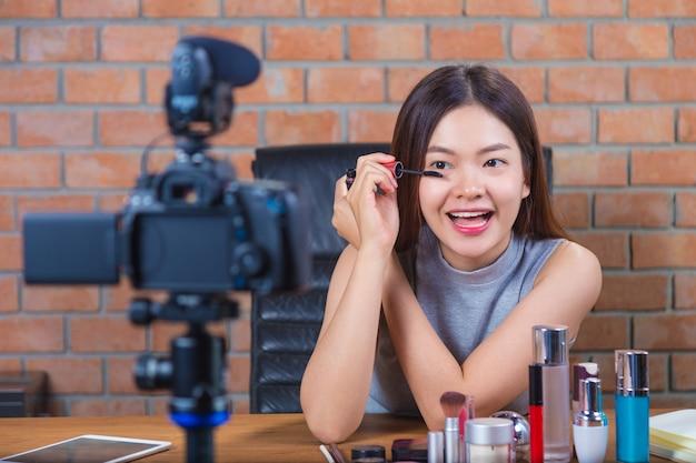 Jonge gelukkige aziatische vrouw die aan haar ventilatorpagina vlogging die toont hoe te om op te zetten