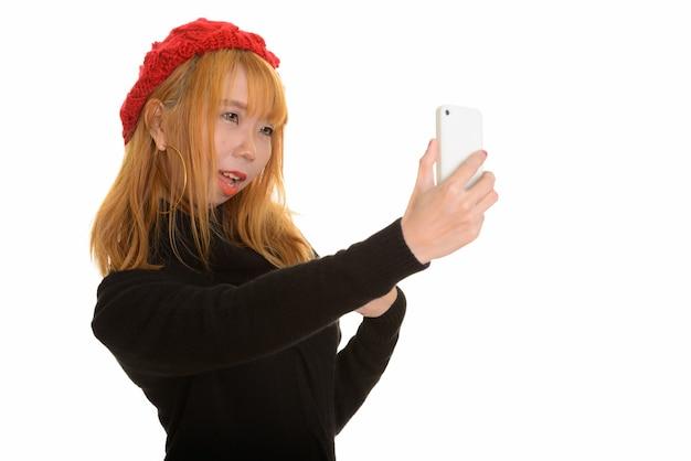 Jonge gelukkige aziatische vrouw die en selfie met mobiele ph glimlacht neemt