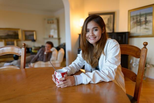 Jonge gelukkige aziatische vrouw die lacht terwijl koffiekopje in comfortabel huis
