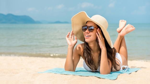 Jonge gelukkige aziatische vrouw met sunhat die bij het strand in de zomer liggen