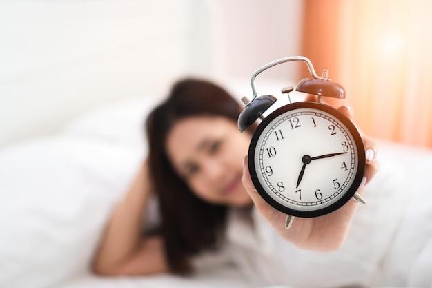 Jonge gelukkige aziatische vrouwenhand die zwarte wekker opheft die van ontwaken in vroege ochtend geniet.