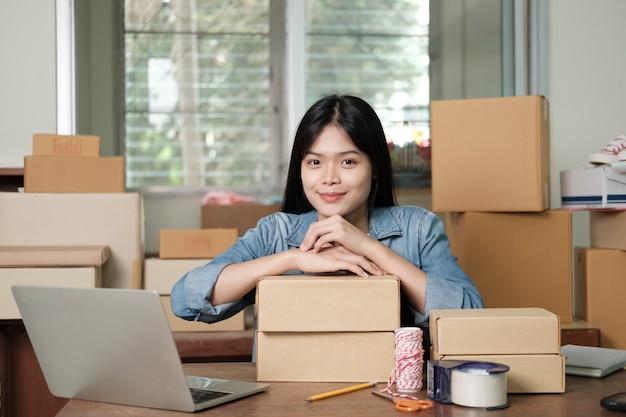 Jonge, gelukkige aziatische zakenvrouw, eigenaar van een bedrijf online met behulp van laptop, ontvangt bestelling van klant met pakketdoosverpakking bij haar startup thuiskantoor, online zakelijke verkoper en bezorging