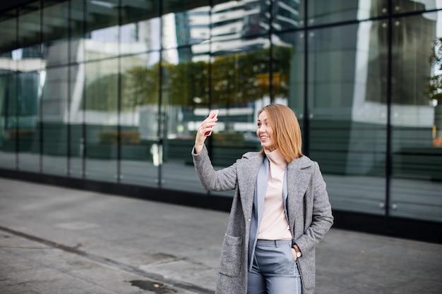 Jonge gelukkige bedrijfsvrouw die videogesprek gebruikt.