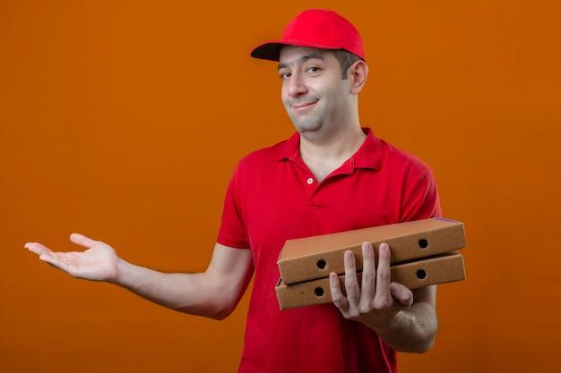 Jonge gelukkige bezorger in rood poloshirt en pet met pizzadozen glimlachend presenteren en wijzen met handpalm kijkend naar de camera over geïsoleerde oranje achtergrond