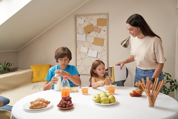 Jonge gelukkige blanke familiemoeder en schattige kleine kinderen die thuis ontbijten, dat zijn ze