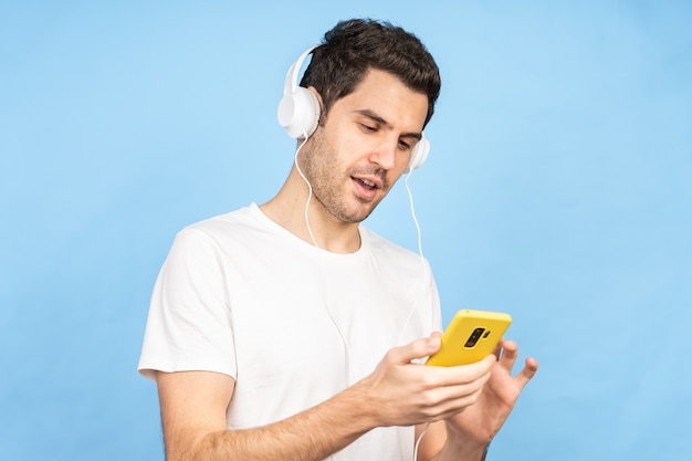Jonge gelukkige blanke man die naar muziek luistert met een koptelefoon tegen een blauwe muur