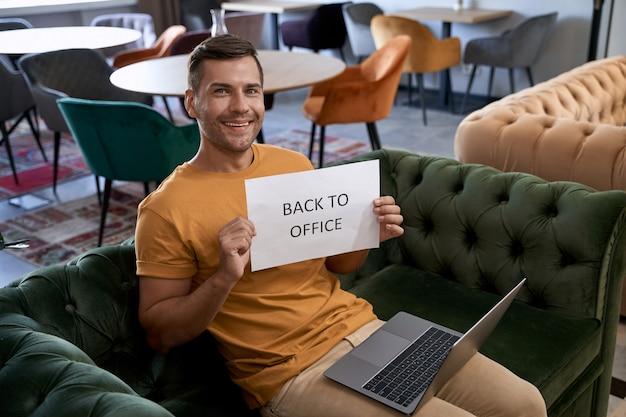 Jonge, gelukkige blanke man die papier met tekst terug naar kantoor laat zien en naar de camera glimlacht terwijl
