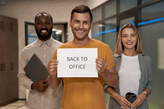 Jonge, gelukkige blanke man kantoormedewerker die papier met tekst terug naar kantoor op de camera toont en