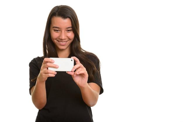 Jonge gelukkige blanke vrouw die en foto met mobiele telefoon glimlacht neemt
