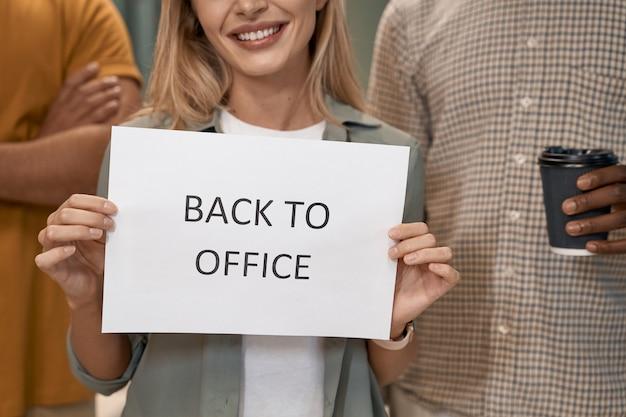Jonge, gelukkige blanke vrouwelijke kantoormedewerker die papier met tekst terug naar kantoor op camera toont