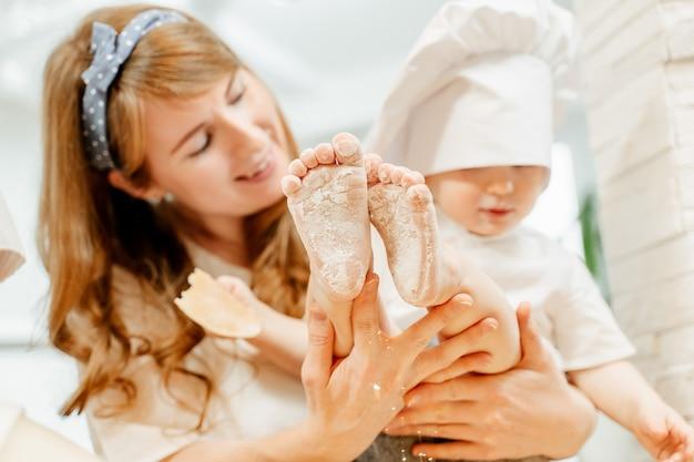 Jonge, gelukkige blanke, wazige moeder houdt in haar handen een grappige rusteloze peuterjongen met schattige voeten in bloem. bakworkshop voor jonge kinderen
