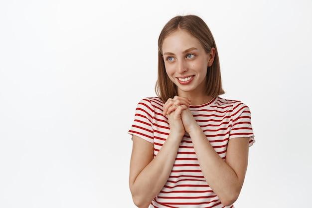 Jonge, gelukkige blonde vrouw bewondert iets, overweegt een prachtig uitzicht, hand in hand, glimlacht en kijkt opzij naar kopieerruimte, witte muur