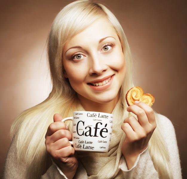 Jonge gelukkige blonde vrouw met koffie en koekjes