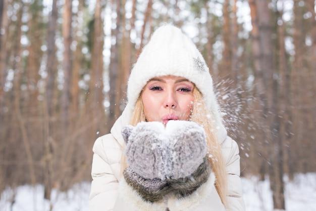 Jonge gelukkige blonde vrouw waait sneeuw in de natuur van de winter
