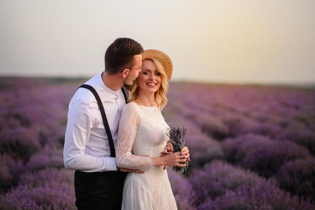 Jonge gelukkige bruid en bruidegom knuffelen in bloeiende lavendelblauwe veld