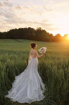 Jonge gelukkige bruid in kanten trouwjurk houdt boeket bloemen, kijkt erop en vormt in de zomer zonsondergang buitenshuis