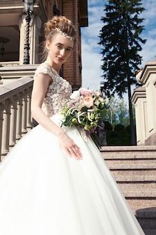Jonge gelukkige bruid met een bruiloft boeket staat op de marmeren trap.