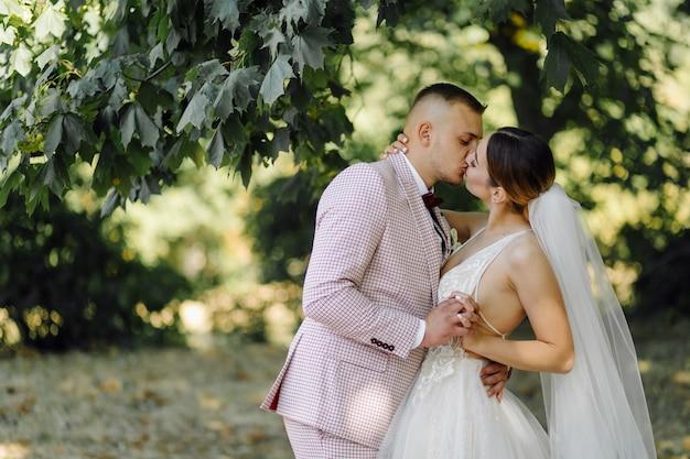 Jonge gelukkige bruidspaar. kaukasische bruid en bruidegom omarmen