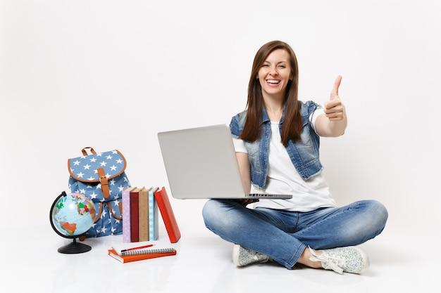 Jonge gelukkige dolblije vrouw student met laptop pc-computer met duim omhoog zittend in de buurt van globe, rugzak, schoolboeken geïsoleerd