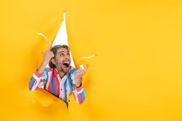 Jonge gelukkige emotionele bebaarde man in een gescheurd gat en vrije ruimte in geel papier