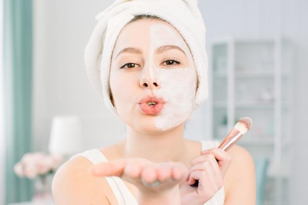 Jonge gelukkige en glimlachende mooie vrouw die klei gezichtsmasker toepast op de helft van het gezicht en een luchtkus verzendt