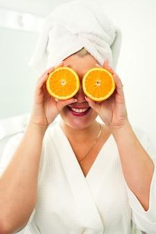 Jonge gelukkige energieke vrouw in een wit gewaad en een handdoek op haar hoofd houdt helften sinaasappels in haar h...