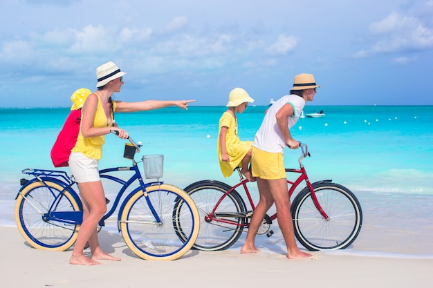 Jonge gelukkige familie berijdende fietsen op tropisch strand