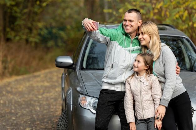Jonge gelukkige familie die een selfie in aard neemt