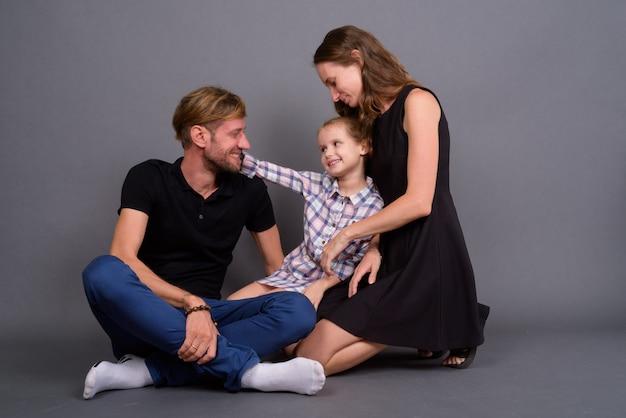 Jonge gelukkige familie die samen tegen grijze muur plakken