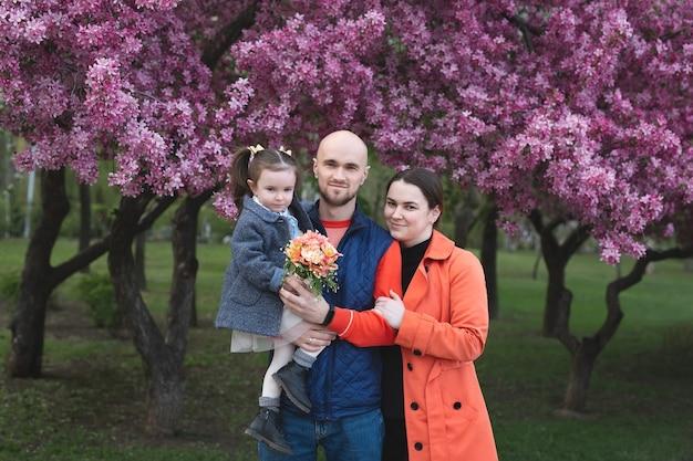 Jonge gelukkige familie in het park in het voorjaar op de achtergrond van een bloeiende boom