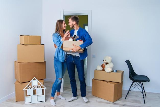 Jonge gelukkige familie met kartondozen die deur van hun nieuw huis openen en bij lege vlakte binnenkomen.