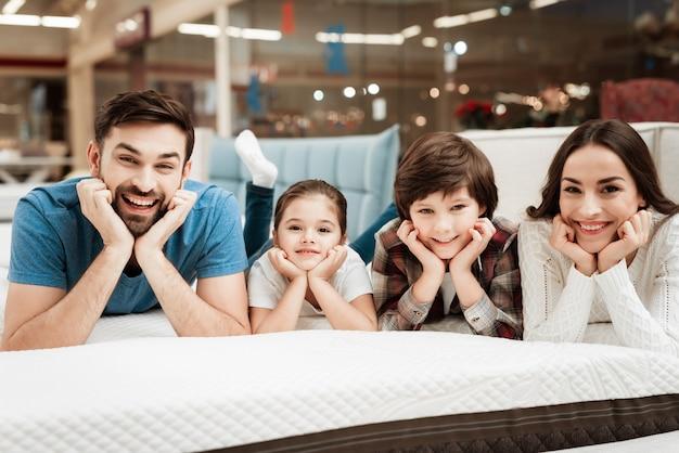 Jonge gelukkige familie ontspannen op zacht bed in winkel