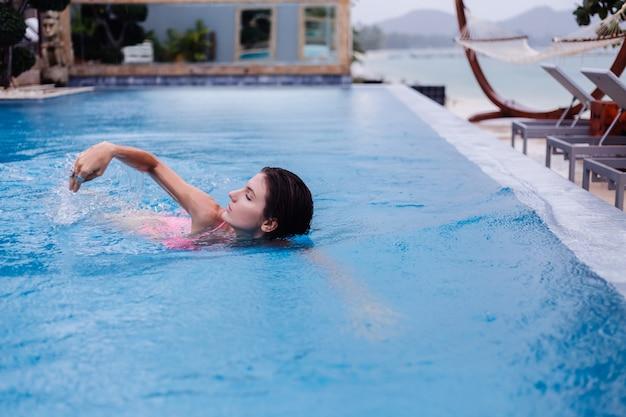 Jonge gelukkige fit slanke europese vrouw in helder roze bikini blauw zwembad