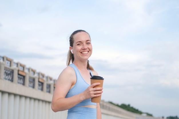 Jonge gelukkige fitnessvrouw die in de stad loopt terwijl ze naar muziek luistert in oortelefoons, kopje koffie vasthoudt. hoge kwaliteit foto