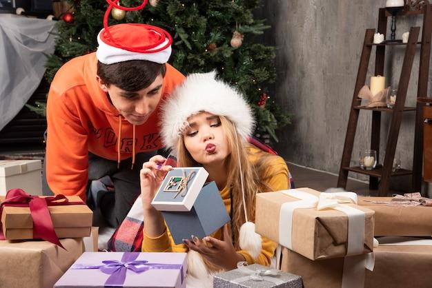 Jonge gelukkige geliefden kijken naar kerstcadeaus in de woonkamer.