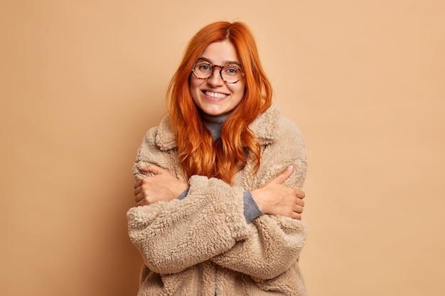 Jonge gelukkige gember jonge blanke vrouw gekleed in een gezellige bontjas omhelst zichzelf om warm te voelen geniet van haar wintervakantie.