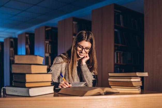 Jonge gelukkige glimlachende student die in glazen voor het examen voorbereidingen treft. meisje in de avond zit aan een tafel in de bibliotheek met een stapel boeken, glimlachen en kijken
