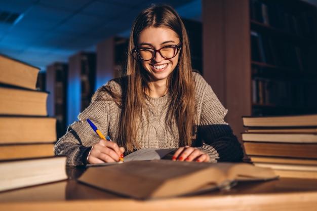 Jonge gelukkige glimlachende student die in glazen voor het examen voorbereidingen treft. meisje in de avond zit aan een tafel in de bibliotheek met een stapel boeken