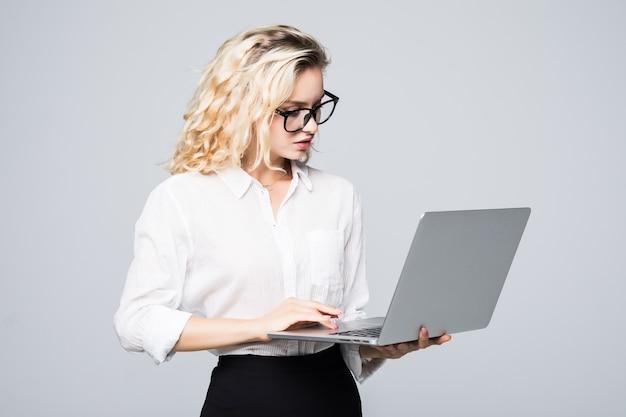 Jonge gelukkige glimlachende vrouw die in vrijetijdskleding laptop houdt en e-mail verzendt naar haar beste vriend