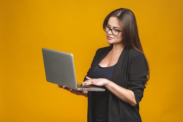 Jonge gelukkige glimlachende vrouw in vrijetijdskleding die laptop houdt en e-mail verzendt naar haar beste vriend die tegen gele muur wordt geïsoleerd.