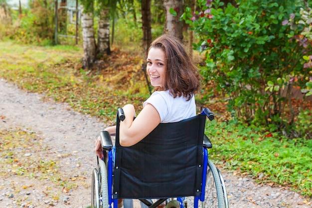 Jonge gelukkige handicapvrouw in rolstoel op weg in het ziekenhuispark dat op geduldige diensten wacht
