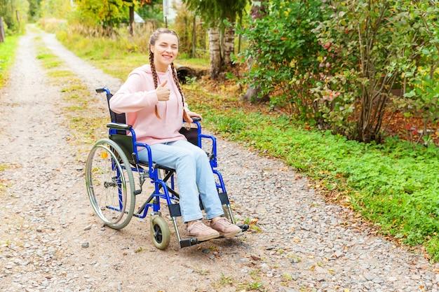 Jonge gelukkige handicapvrouw in rolstoel op weg in het ziekenhuispark die op de geduldige diensten wachten. verlamd meisje in invalide stoel voor gehandicapten buiten in de natuur. revalidatie concept.