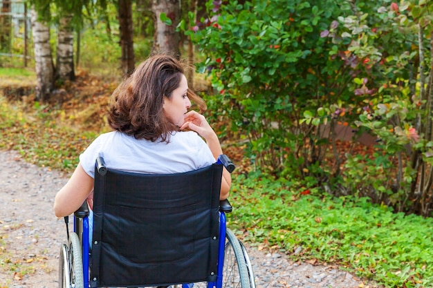 Jonge gelukkige handicapvrouw in rolstoel op weg in het ziekenhuispark die van vrijheid genieten