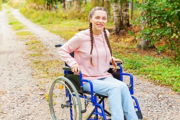 Jonge gelukkige handicapvrouw in rolstoel op weg in het ziekenhuispark