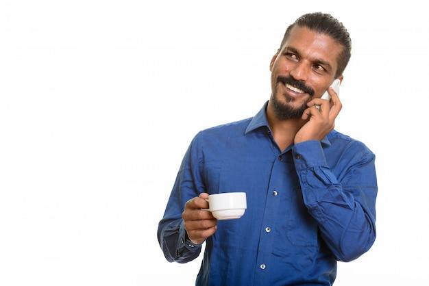 Jonge gelukkige indische zakenman die op mobiele telefoon spreekt en koffiekop houdt terwijl het denken