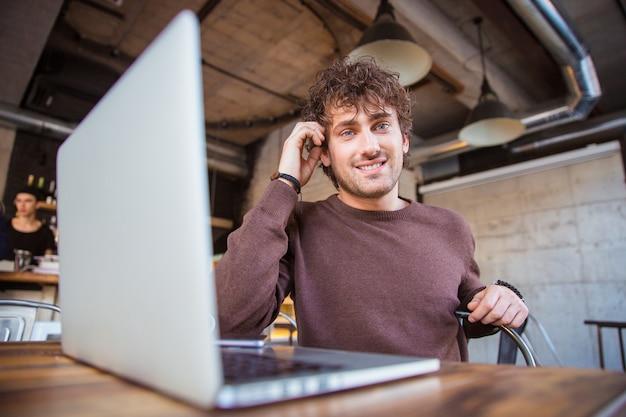 Jonge gelukkige inhoud aantrekkelijke vrolijke lachende knappe man aan het werk met behulp van laptop