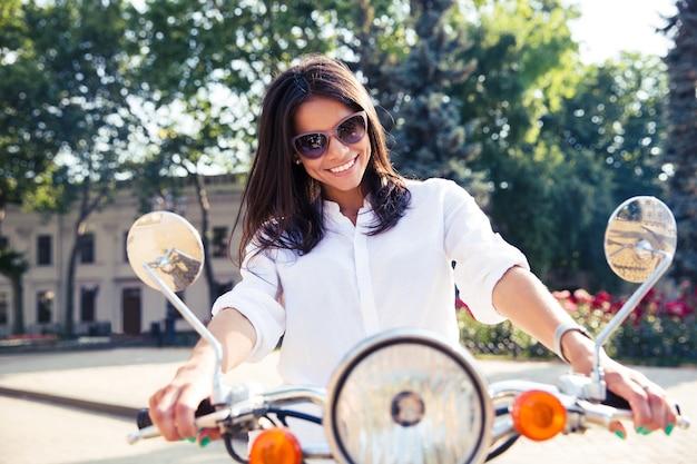 Jonge gelukkige italiaanse vrouw rijdt op een scooter in de stad
