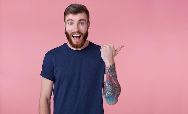 Jonge, gelukkige jonge kerel met een rode baard, met wijd open mond van verbazing, zag iets verkeerds, wil je aandacht vestigen met wijzende vinger om ruimte aan de rechterkant te kopiëren die over roze achtergrond wordt geïsoleerd.