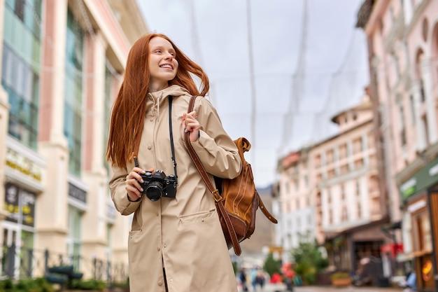 Jonge gelukkige jonge roodharige reiziger vrouw met retro filmcamera in handen, wandelen in een stedelijke straat alleen, beige jas, casual outfit dragen. leuke blanke dame brengt weekend door in de oude stad?