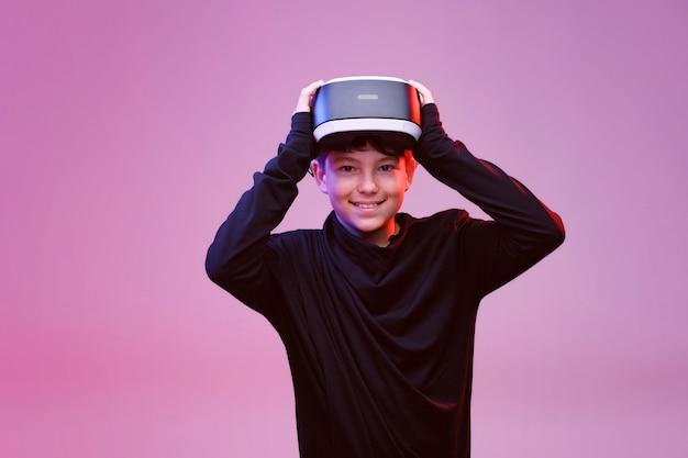 Jonge gelukkige jongen in een bril van virtual reality op neol lichte achtergrond